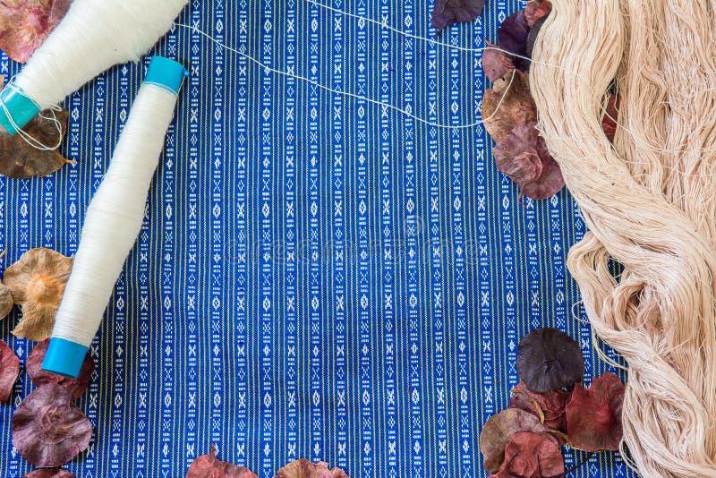 Тайский поток silk ткани и сухие лист на предпосылке и текстуре ткани старой картины тайских стоковое изображение rf