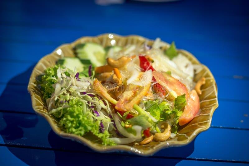 Тайский салат вермишели с томатом, луком и мясом в коричневом блюде изолированном на голубой таблице стоковая фотография rf