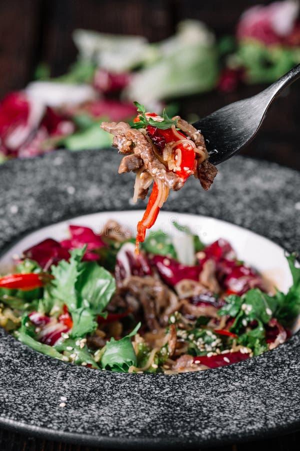 Тайский салат с teriyaki говядины и свежие овощи на вилке в fr стоковые фотографии rf