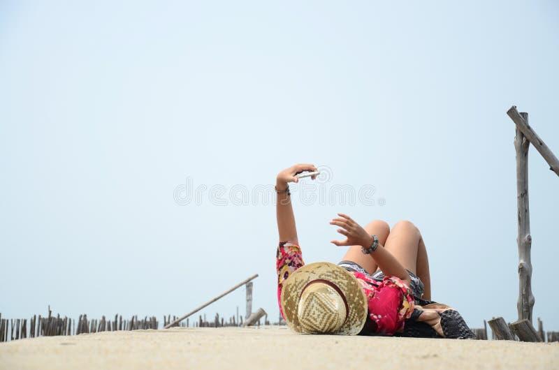 Тайский сон женщин играя мобильный телефон самостоятельно на мосте дорожки стоковые фотографии rf