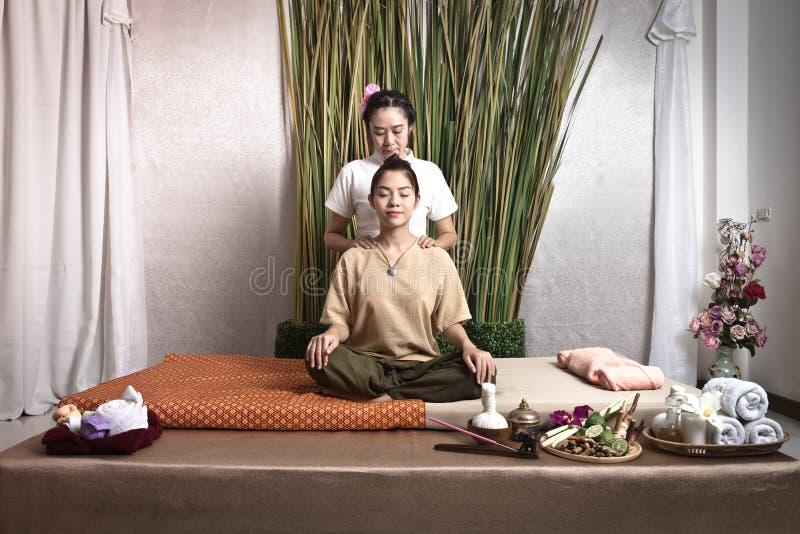 Тайский Masseuse делая массаж для женщины в салоне курорта Азиатская красивая женщина получая тайский травяной массаж обжатия мас стоковое фото rf