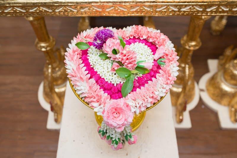 Тайское сердце цветка сформировало гирлянду на золотом подносе с пользой постамента для благословленной воды в тайской свадебной  стоковые изображения rf