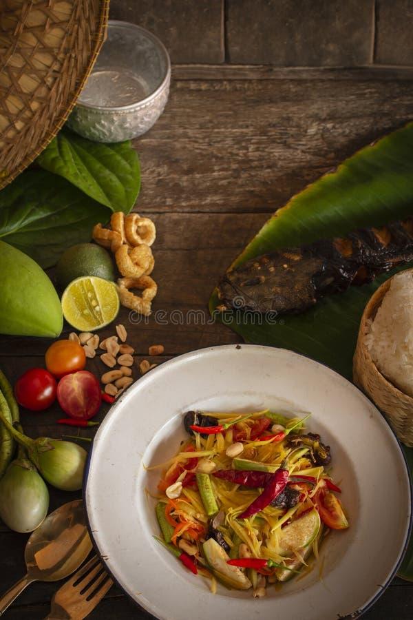 Тайцы животика сома салата папапайи на белой плите zine помещенной на деревянной таблице там баклажан, томат, лимон, зажаренная р стоковые изображения rf