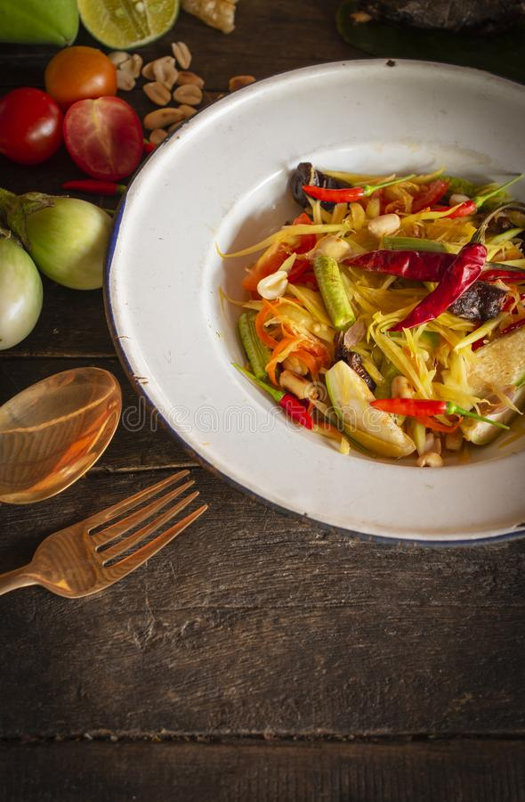 Тайцы животика сома салата папапайи на белой плите zine помещенной на деревянной таблице там баклажан, томат, лимон, вилка, ложка стоковые изображения