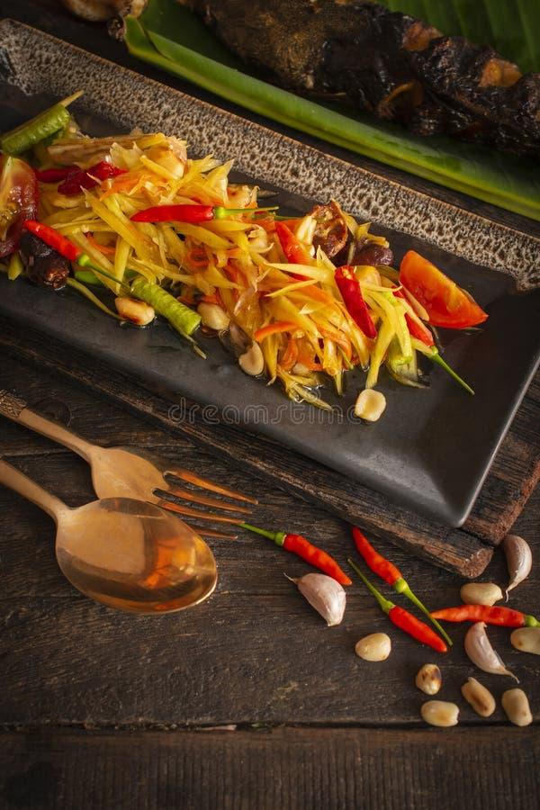Тайцы животика сома салата папапайи на квадратной черной плите помещенной на деревянной таблице там фасоль, зажаренная рыба, чесн стоковые изображения