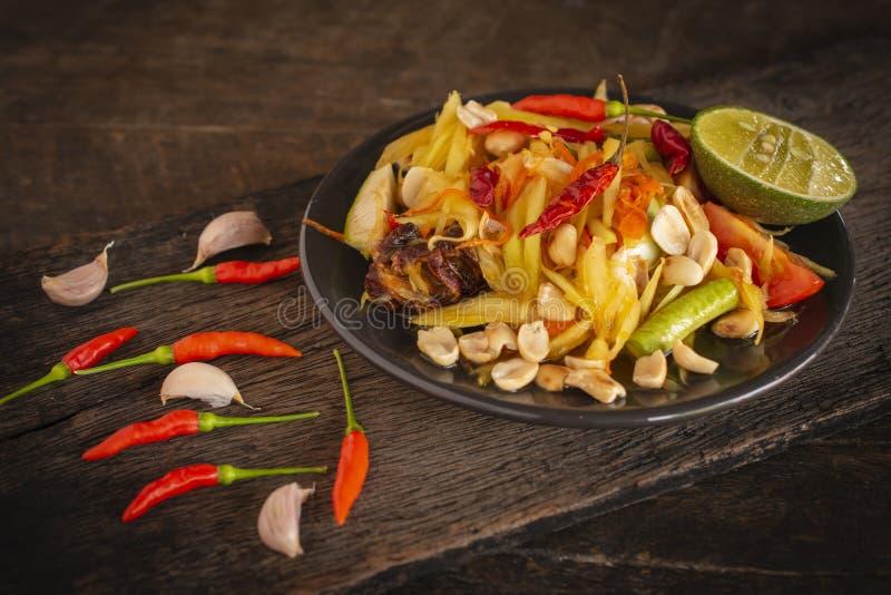 Тайцы животика сома салата папапайи на черной плите помещенной на деревянной таблице там чеснок и чили помещенные рядом с стоковые фото