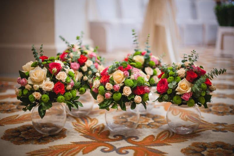 5 таких же букетов пестротканых роз в вазах стоковая фотография