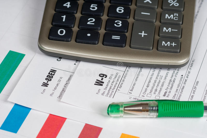 Таксируйте формы отчетности с зелеными ручкой и калькулятором стоковая фотография