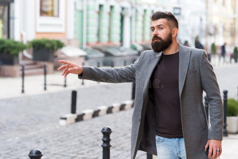 Такси бизнесмена улавливая пока стоящ outdoors городская предпосылка Непринужденного стиля хипстера человека такси бородатого жда стоковые фотографии rf