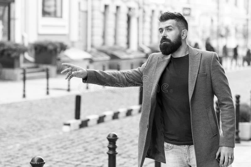 Такси бизнесмена улавливая пока стоящ outdoors городская предпосылка Непринужденного стиля хипстера человека такси бородатого жда стоковая фотография rf