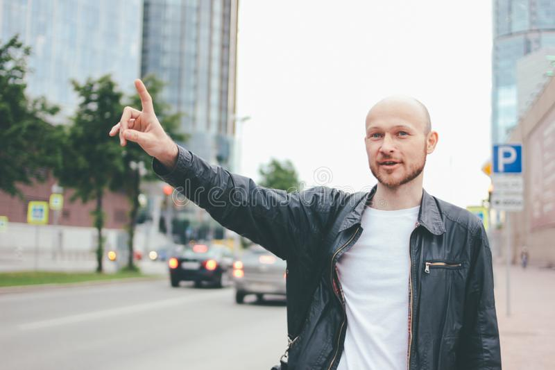 Такси взрослого привлекательного лысого бородатого человека улавливая в улице города стоковое фото rf