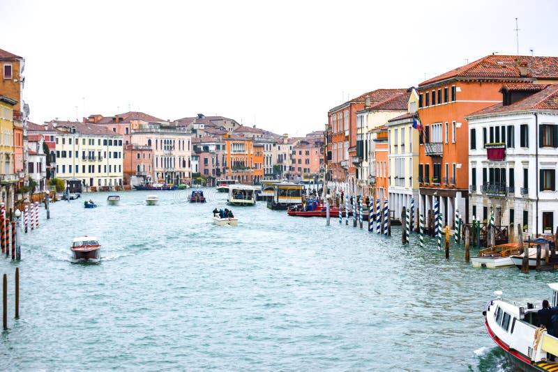 Такси воды и другие шлюпки плавая между венецианскими зданиями вдоль большого канала в Венеции, Италии стоковое фото rf