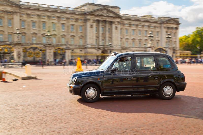 Такси Лондона вне Букингемского дворца стоковое фото rf