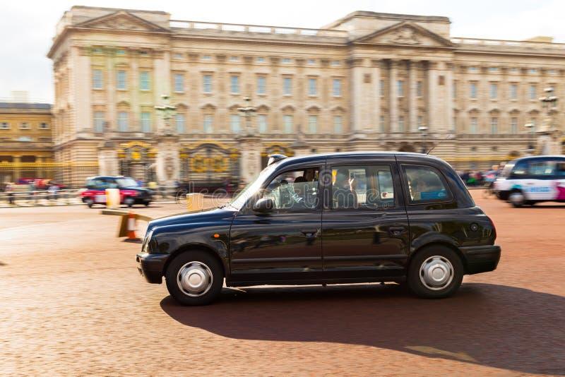 Такси Лондона вне Букингемского дворца стоковые фото