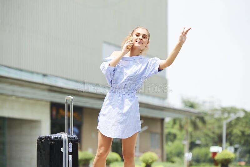 Такси милой женщины улавливая в аэропорт стоковые фотографии rf
