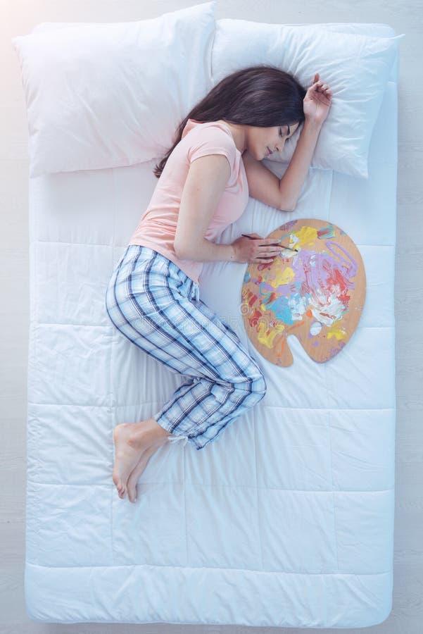 Талантливая девушка спать в кровати с щеткой палитры и картины стоковое изображение