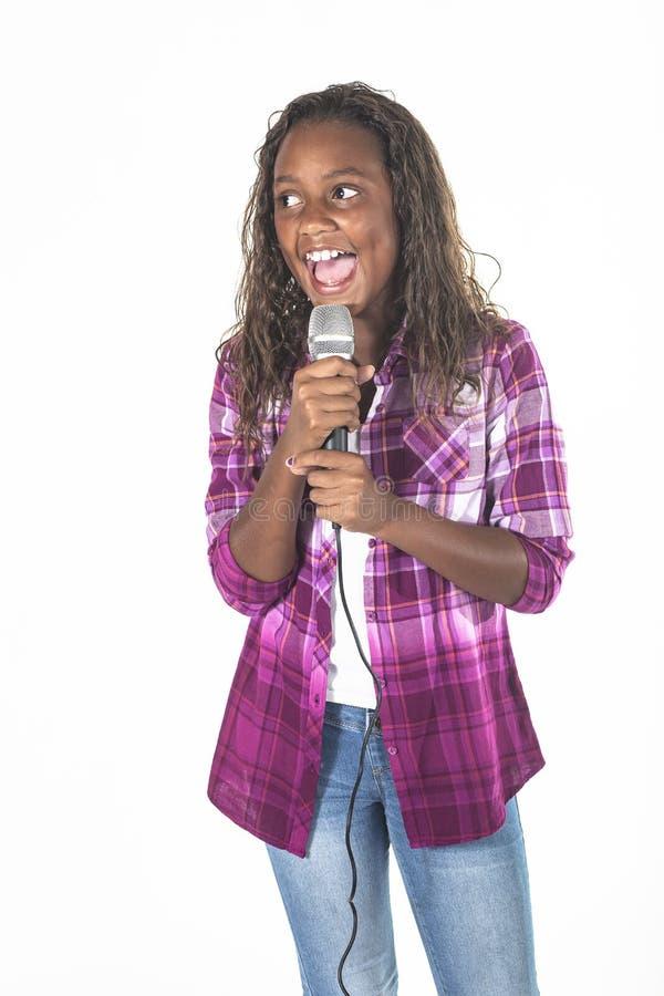 Талантливый молодой певец поет в микрофон стоковое фото