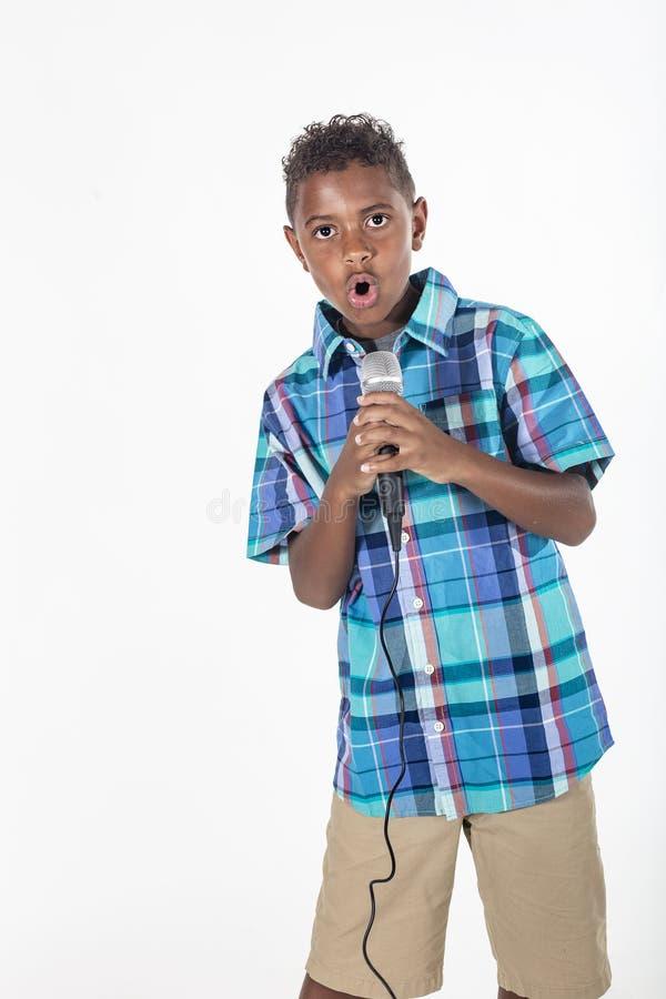 Талантливый молодой певец поет в микрофон стоковые фото
