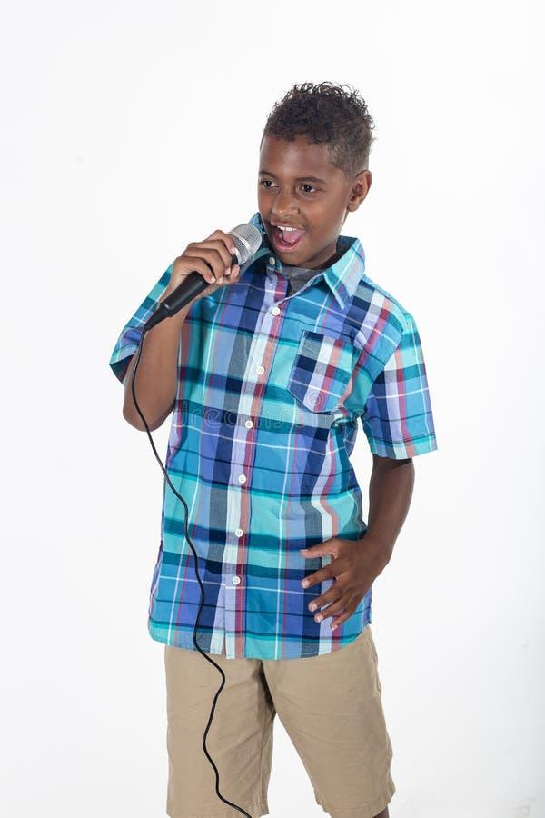 Талантливый молодой певец поет в микрофон стоковые изображения