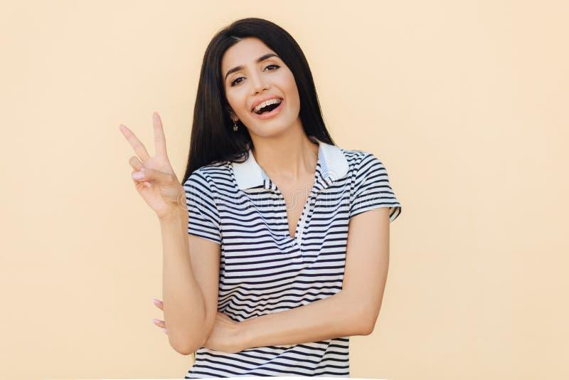 Талия вверх по портрету женщины счастливого брюнет молодой показывает знак мира, улыбки счастливо на камере, носит расчалки на зу стоковая фотография