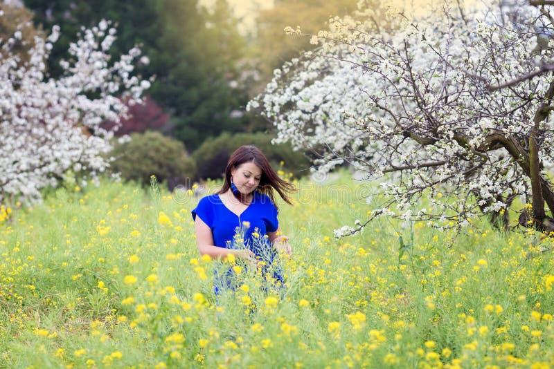Талия вверх по портрету молодой женщины в яркой голубой верхней части в blossoming саде и желтый мустард field, усмехаться, смотр стоковое изображение