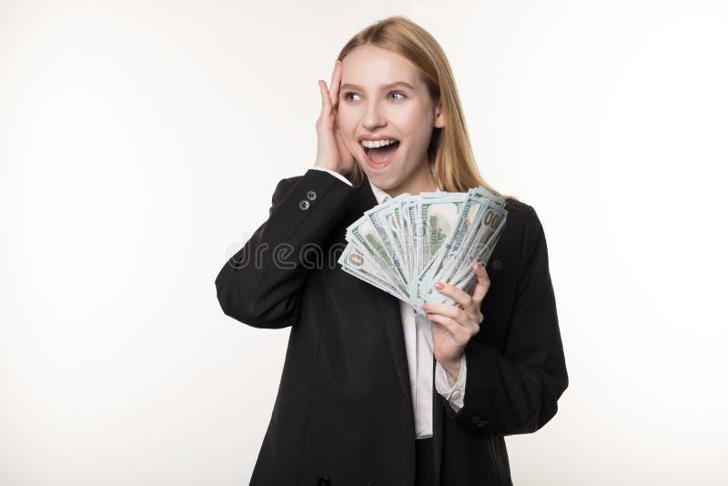 Талия вверх по портрету счастливой удовлетворенной девушки в черном пуке удерживания костюма банкнот и смотреть денег прочь стоковое изображение