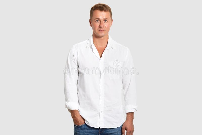 Талия вверх по съемке привлекательного мужского предпринимателя носит белую рубашку и джинсы, держат руку в кармане, изолированно стоковое фото rf