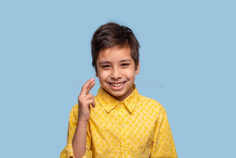 Талия вверх по эмоциональному портрету смешного мальчика предлагая желание и показывая руку с пересеченными пальцами, изолированн стоковые изображения rf
