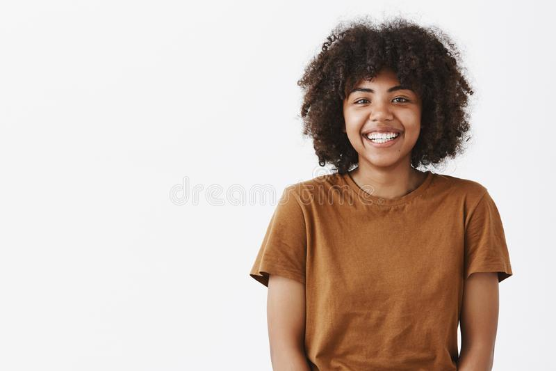 Талия-вверх сняла милого беспечального выглядящего дружелюбн Афро-американского девочка-подростка с афро стилем причёсок усмехаяс стоковое фото rf