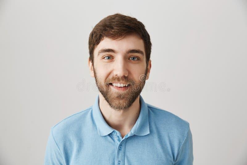 Талия-вверх сняла смешного эмотивного взрослого бородатого парня в голубой рубашке поло, делающ стороны, усмехающся обширно и мел стоковые фотографии rf