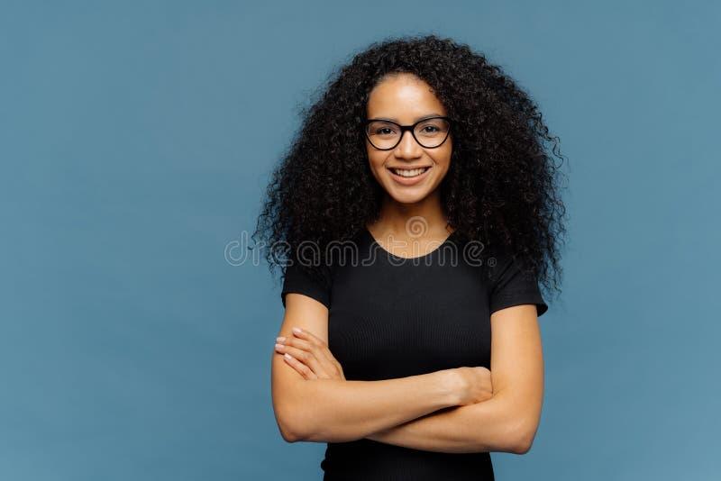 Талия вверх сняла усмехаясь Афро американская женщина имеет оружия быть сложенным, носит зрелища и случайная черная футболка, нас стоковое изображение