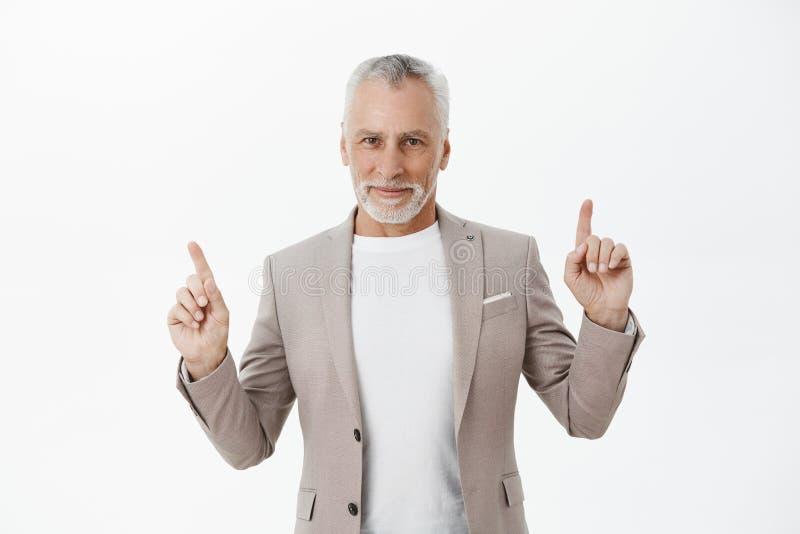 Талия-вверх снятая ассерторического приятного и счастливого уверенного старика с серой бородой и волос в костюме поднимая указате стоковое фото