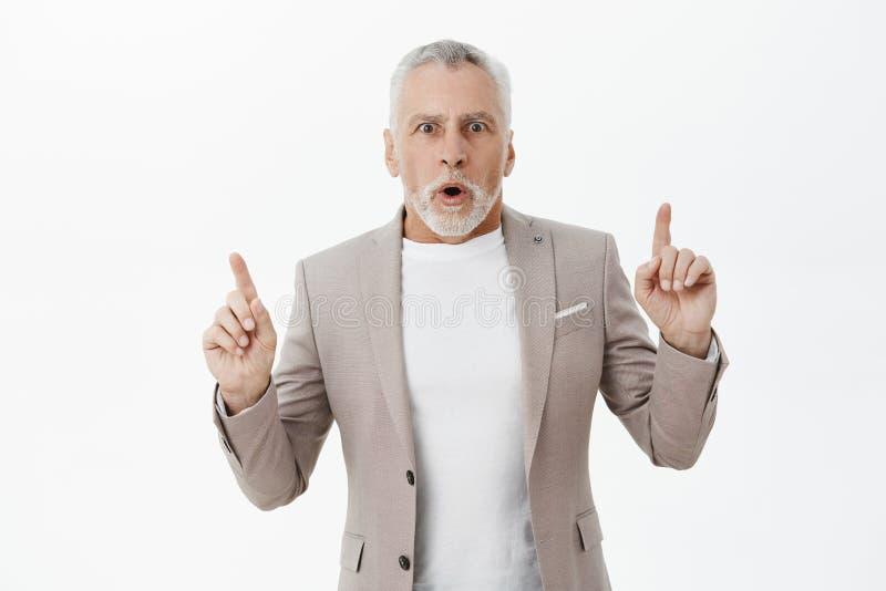 Талия-вверх снятая оглушенного волнующего сотрясенного дедушки в костюме над футболкой с ртом серой бороды и короткого стиля прич стоковое фото