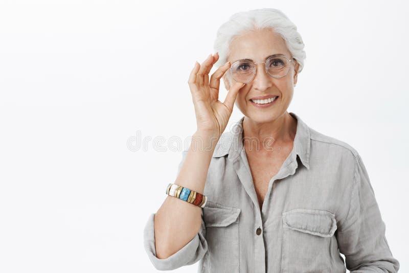 Талия-вверх снятая очаровательного вида и славной бабушки в стеклах видимости касаясь оправе eyewear и усмехаясь joyfully помогаю стоковые изображения