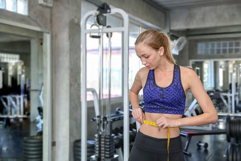 Талия молодой кавказской женщины измеряя в спортзале Тонкая женщина измеряя ее тонкую талию с рулеткой усмехаясь люди с измерение стоковое изображение rf