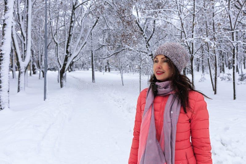 Тали-съемка счастливой и стильной красивой женщины в яркой куртке коралла, усмехаясь и наслаждаясь зимним днем стоковые изображения rf