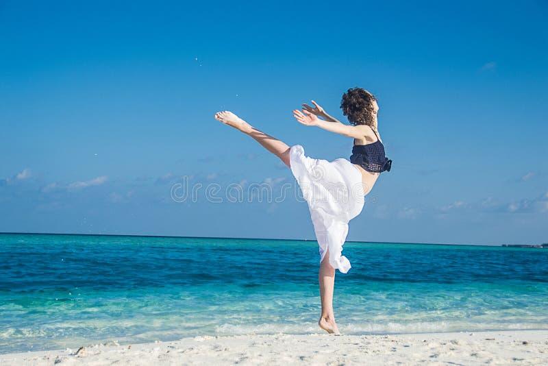 Танец маленькой девочки на тропическом пляже стоковое изображение rf