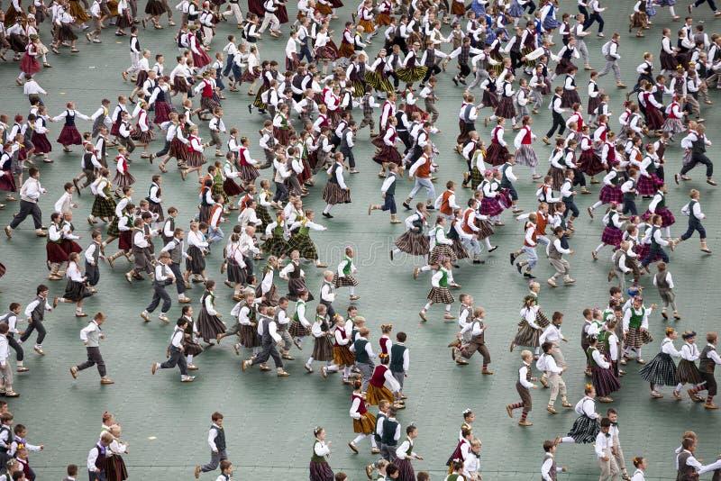 Танцоры в традиционных костюмах выполняют на грандиозном концерте народного танца латышской песни молодости и танцуют фестиваль в стоковые фотографии rf