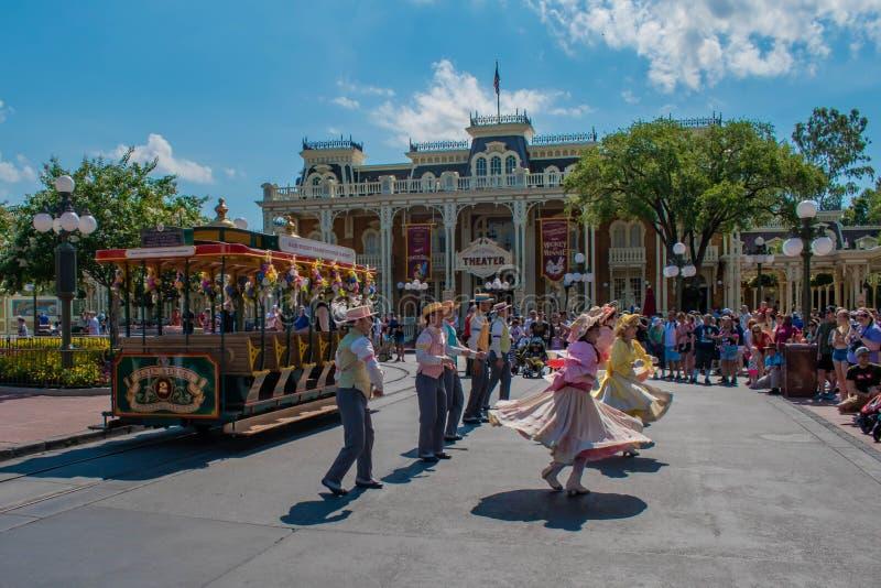 Танцоры с красочными и винтажными костюмами на городской площади в волшебном королевстве в зоне 2 мира Уолт Дисней стоковая фотография rf