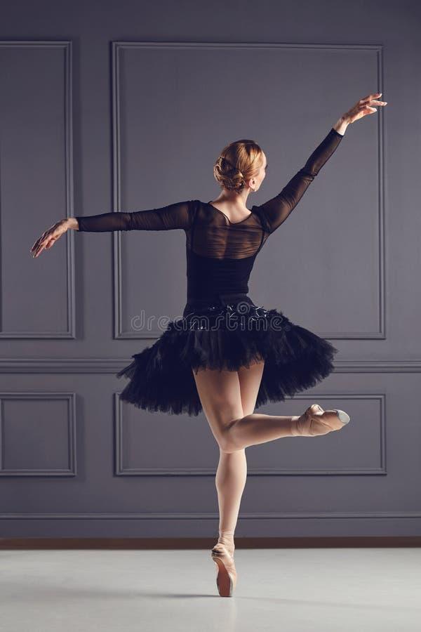 Танцор балерины в черном платье представляя над серой предпосылкой стоковая фотография rf