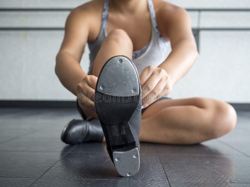Танцор кладя на ее ботинки крана стоковые изображения rf