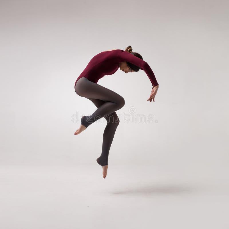 Танцор молодой женщины в maroon скакать купальника стоковое фото rf