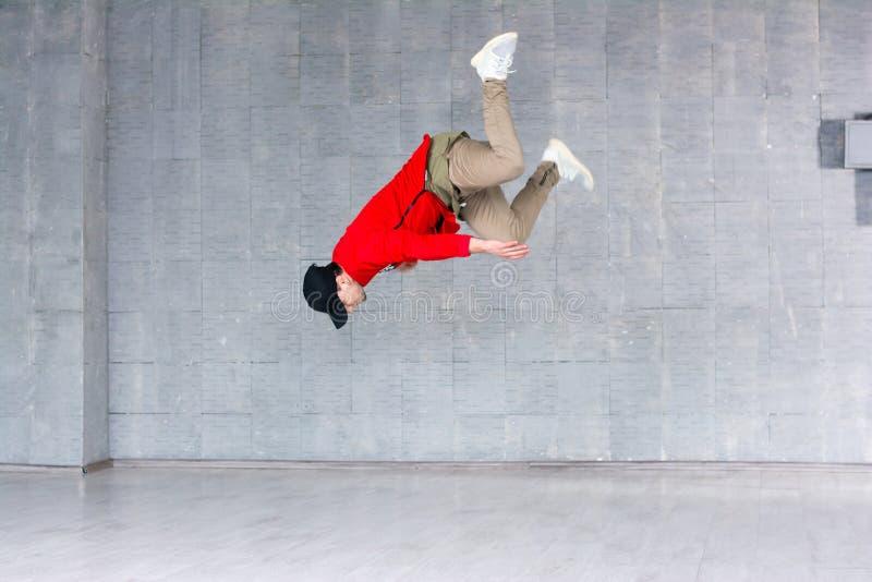 Танцор рэпа скача на серую предпосылку стоковая фотография