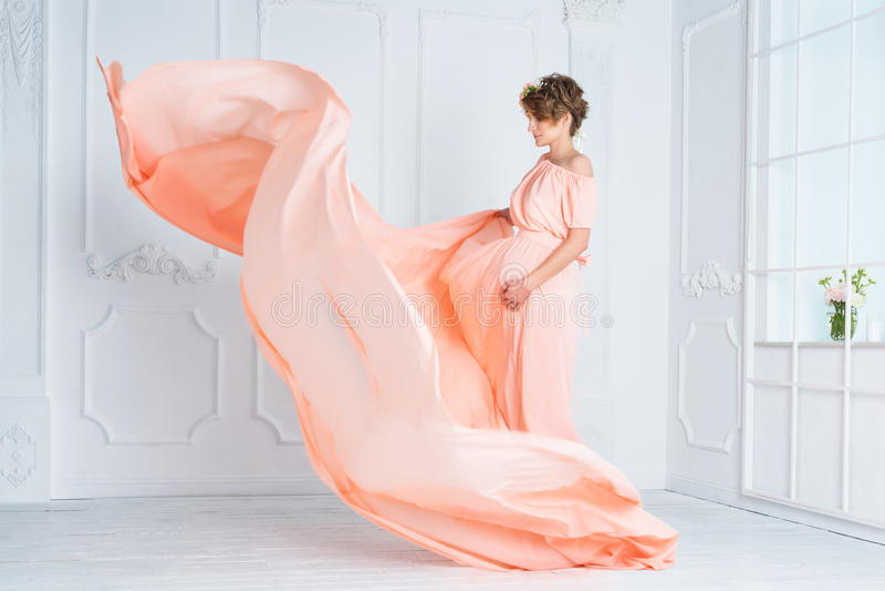 Танцы беременной женщины в розовом летании платья вечера на ветре Развевая ткань, съемка моды стоковые фото