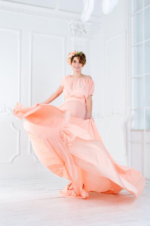 Танцы беременной женщины в розовом летании платья вечера на ветре Развевая ткань, съемка моды стоковое фото rf