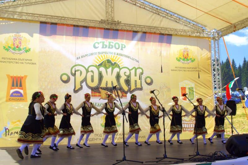 Танцы группы фольклора женщин на этапе Rozhen, Болгарии стоковые фото