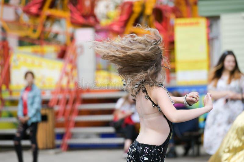 Танцы девушки брюнета на улице Портрет красивого белокурого outdoors в умном платье, образа жизни стоковые фотографии rf