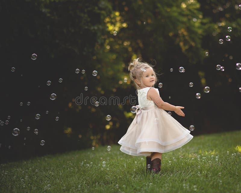 Танцы маленькой девочки в пузырях стоковая фотография rf