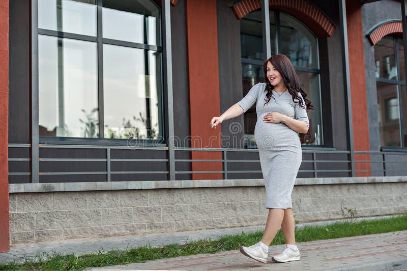 Танцы молодой беременной женщины идя вдоль окон города стоковое изображение rf