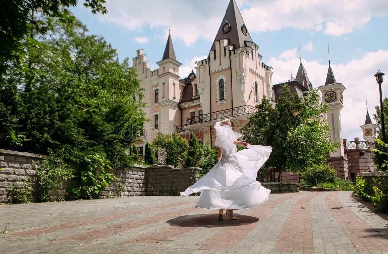 Танцы невесты закручивая о красивом здании стоковые фото